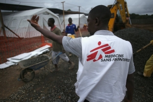 A Doctors Without Borders staffer supervises as construction workers complete the new Ebola treatment center on August 17, 2014 near Monrovia, Liberia.